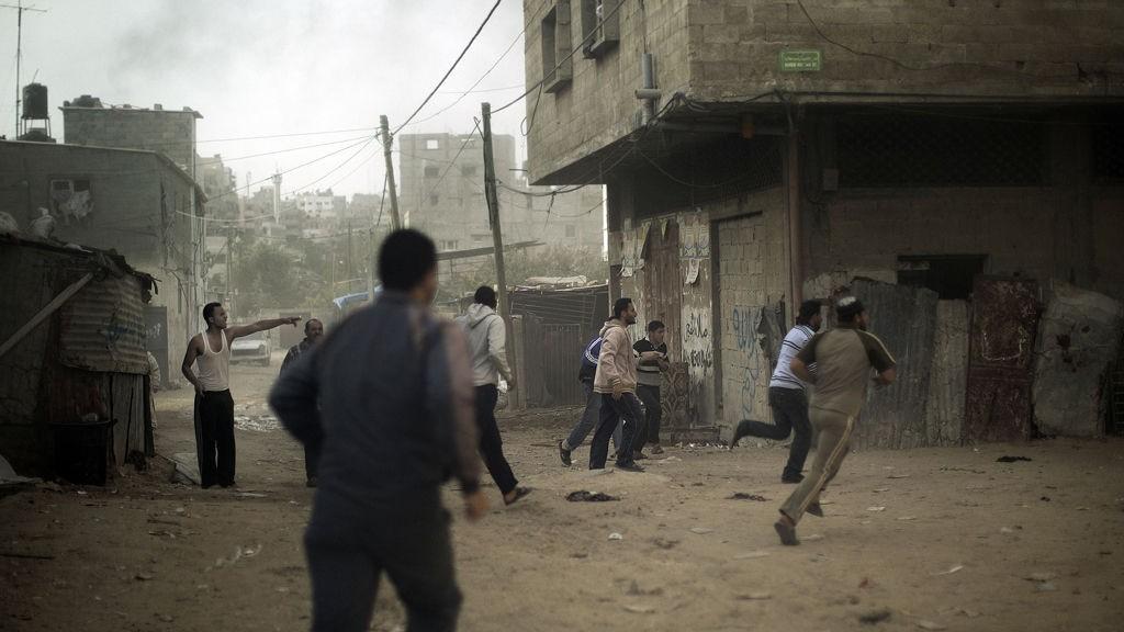Palestinere løper for å søke ly etter et israelsk luftangrep mot Gaza by fredag.