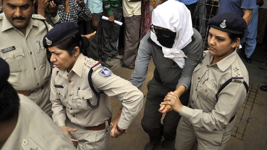 A Swiss woman, center, who, according to police, was gang-raped by a group of eight men while touring by bicycle with her husband, is escorted by policewomen for a medical examination at a hospital in Gwalior, in the central Indian state of Madhya Pradesh, Saturday, March 16, 2013. Thirteen men were detained and questioned in connection with the attack, which occurred Friday night as the couple camped out in a forest after bicycling from the temple town of Orchha, local police officer R.K. Gurjar said. The men beat the couple and gang-raped the woman, he said. They also stole the couple's mobile phone, a laptop computer and 10,000 rupees ($185), Gurjar said. (AP Photo)