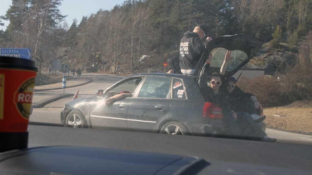 PÅ TAKET: Her sitter to personer i bagasjerommet, og en person sitter på taket, mens bilen kjører på veien inn til Strømstad sentrum.