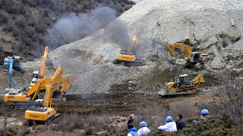 n this photo released by China's Xinhua News Agency, earthmovers remove rocks and mud on the scene where a landslide hit a mining area in Maizhokunggar County of Lhasa, southwest China's Tibet Autonomous Region, on Friday, March 29, 2013. The large landslide trapped dozens of workers in the gold mining area, state media reported