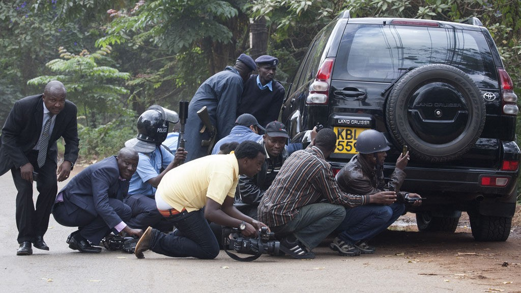 Police officers and members of the media take cover at a distance from the Westgate Shopping Centre after continuous gunfire was heard coming from the mall in Nairobi