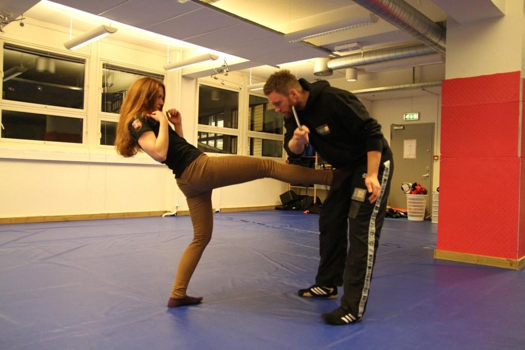 SELVFORSVAR: Anders Hilling får seg et spark i kronjuvelene etter å ha truet Kristin Skarbøvik med kniv. – Dette skaper en åpning for at jeg kommer meg unna, sier hun. Begge to er instruktører i Krav Maga på Oslo Fight Center og holder nå gratis selvforsvarskurs for jenter.