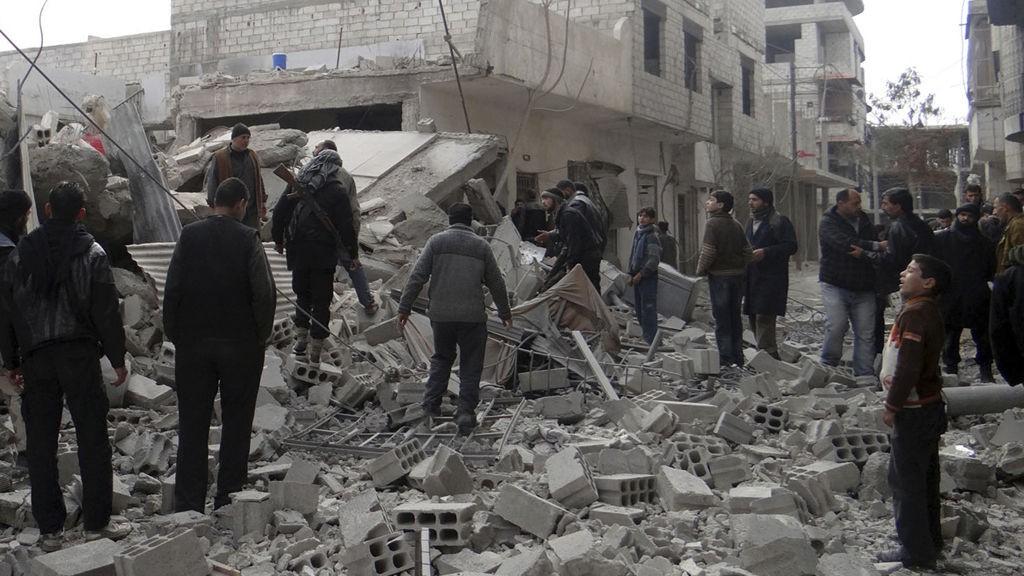 Sivile og opprørssoldater inspiserte tirsdag situasjonen etter at fly fra regjeringsstyrkene angrep forstaden Ghouta ved Damaskus.