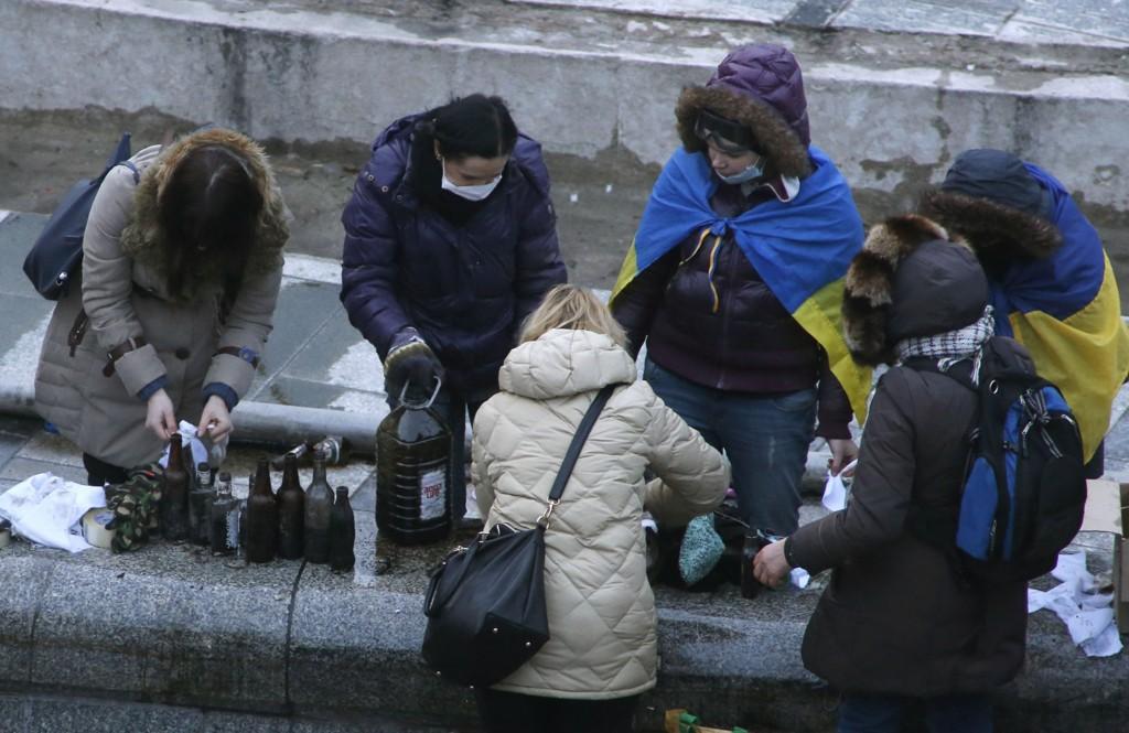 Reuters har tatt et bilde onsdag morgen som viser tilsynelatende helt alminnelige kvinner som står på Uavhengighetsplassen og lager brannbomber.