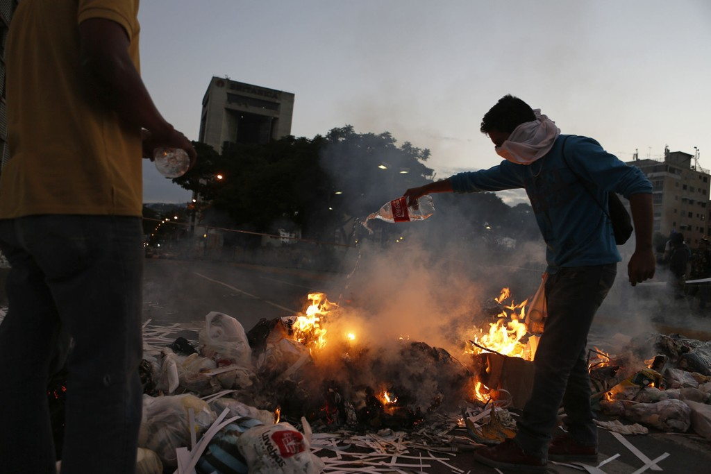 Demonstranter ved en brennende barrikade i Caracas torsdag.