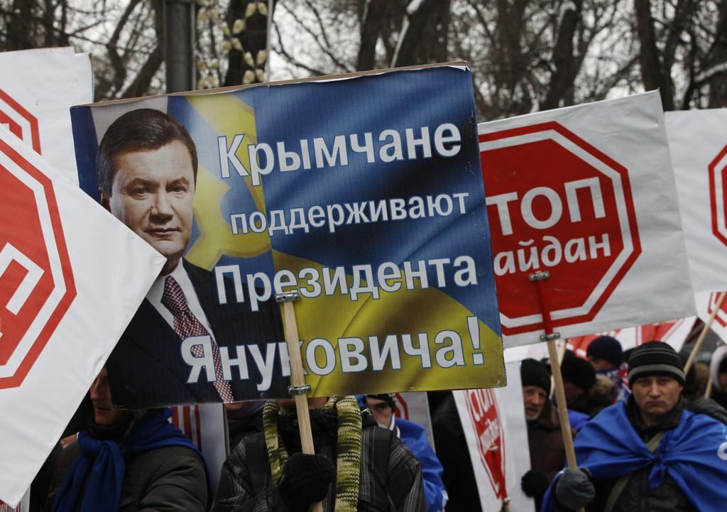 """PRO-RUSSISK: Tilhengere av den da fortsatt sittende pro-russiske presidenten Viktor Janukovitsj med plakater utenfor parlamentet i Kiev 28. januar. På plakaten står det """"Krims innbyggere støtter Janukovitsj""""."""