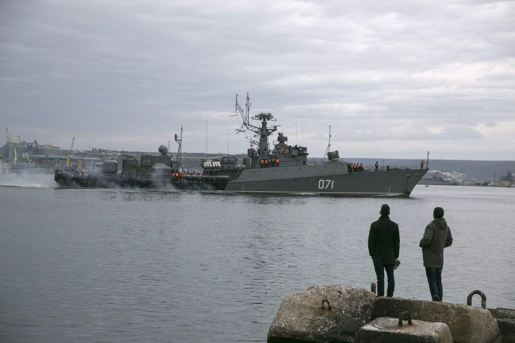 HÅP OM FRED: Mennesker ser på et russisk marinefartøy som ankommer Krim-halvøya.