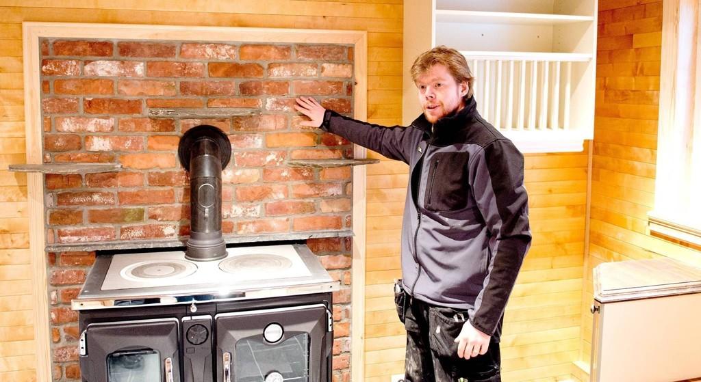 KJØKKEN: En vedovn som varmer opp den vannbårne varmen i huset er plassert på kjøkkenveggen inn mot stuen. Ovnen forvarmer også vannet til varmtvannsberederen. Sammen med solfangere på taket, kommer husets oppvarming hovedsakelig fra denne vedovnen. Teglsteinen bak er fra pipen til hytten som tidligere sto på tomten. - Jeg regner med å bruke lite strøm til oppvarming av huset, sier Ruben Oddekalv.