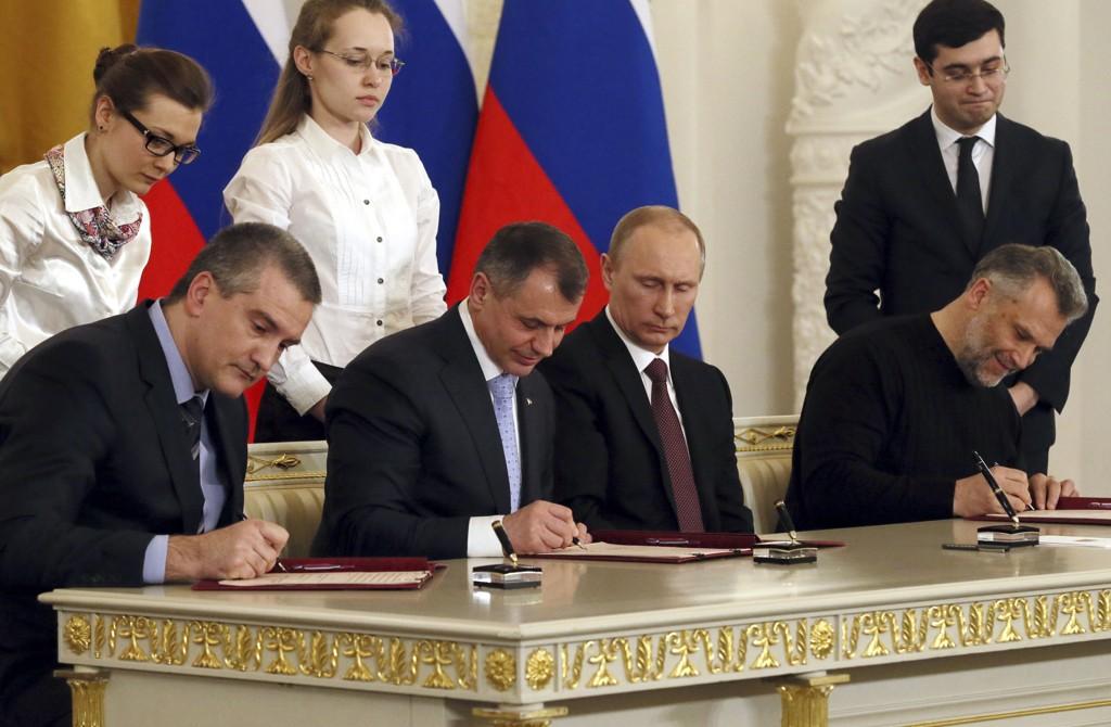 Erklæringen om at Krim-halvøya slutter seg til Russland blir undertegnet av (f.v.) Krim-regionens leder Sergej Aksionov, lederen av regionforsamlingen på Krim, Vladimir Konstantivo, Russlands president Vladimir Putin og borgermesteren i Sevastopol, Aleksej Tsjalij.