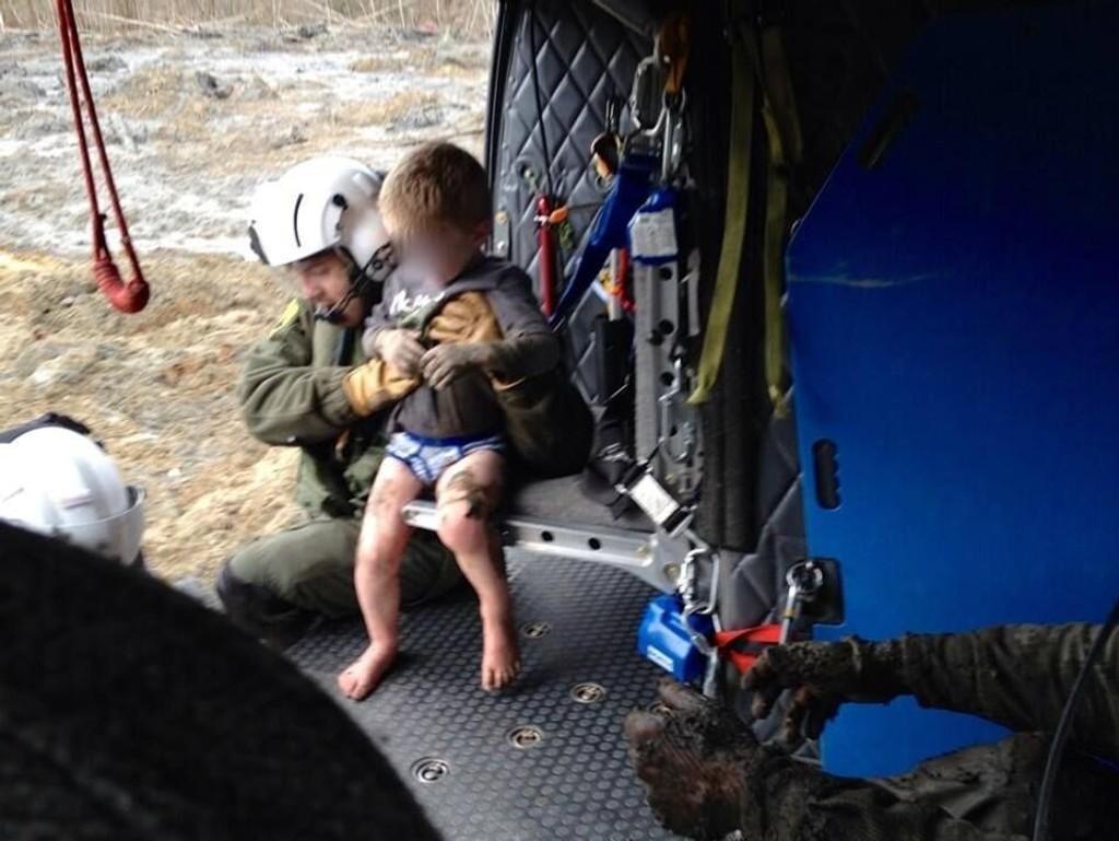 REDDET: Redningsmannskaper tar hånd om gutten som ble rammet av det dødelige jordskredet i Washington forrige helg.