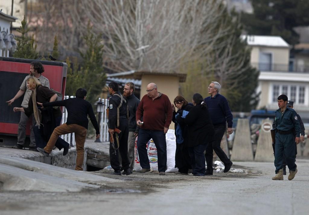 En afghansk politimann evakuerer flere utlendinger vekk fra angrepsstedet i den afghanske hovedstaden Kabul.