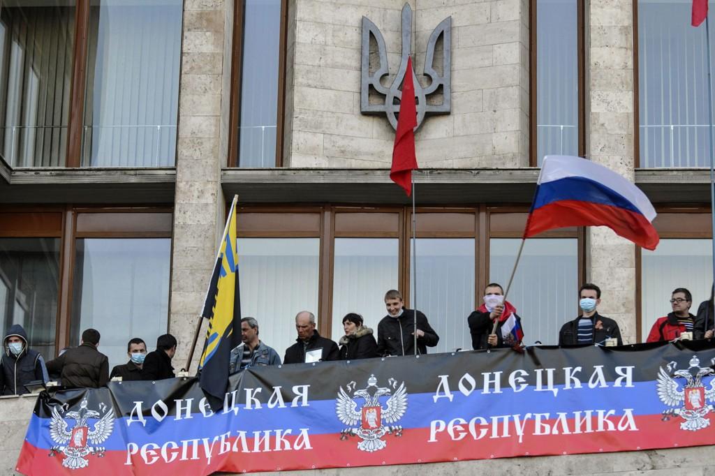 Demonstranter hang opp et banner hvor det står skrevet «Republikken Donetsk» på den okkuperte bygningen i den øst-ukrianske gruvebyen søndag.