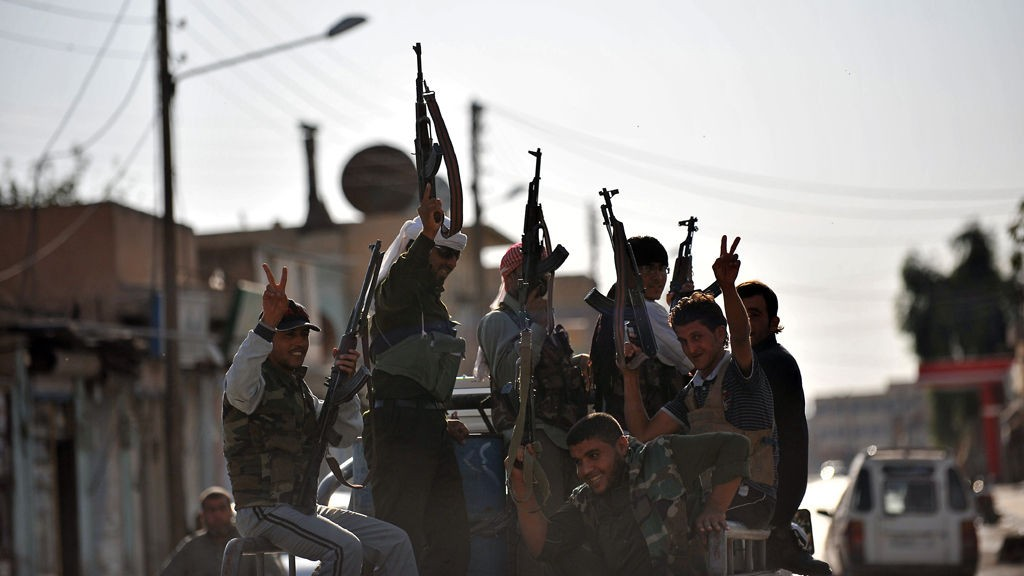 Norske statsborgere som har reist til Syria for å kjempe mot Assad-regimet, har kriget sammen med en av landets mest beryktede opprørsgrupper. Illustrasjonsbilde: Syriske opprørere patruljerer en gate i byen Tal Abyad nær grensen til Tyrkia.