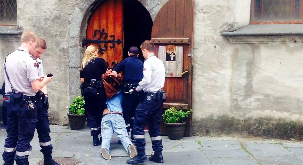 INGEN BØNN: For å få kontroll over den angressive mannen og skjerme ham fra folkemengden, valgte politiet å dra ham inn til inngangspartiet i Korkskirken mens de ventet på en marje.