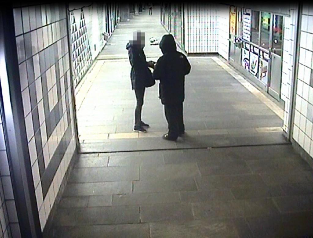 TRUET MED TANG: Her gir kvinnen fra seg mobilen og lommeboken sin etter at mannen truet henne med det hun oppfattet som en kniv. Foto: Politiet