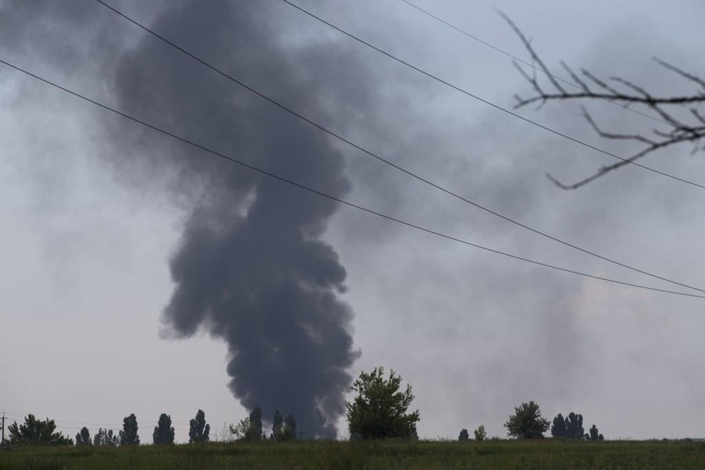 I BAKKEN: Svart røyk stiger opp fra stedet hvor det ukrainske helikopteret styrtet etter angivelig å ha blitt truffet av en rakett. 12 personer omkom ifølge ukrainske talspersoner i angrepet.