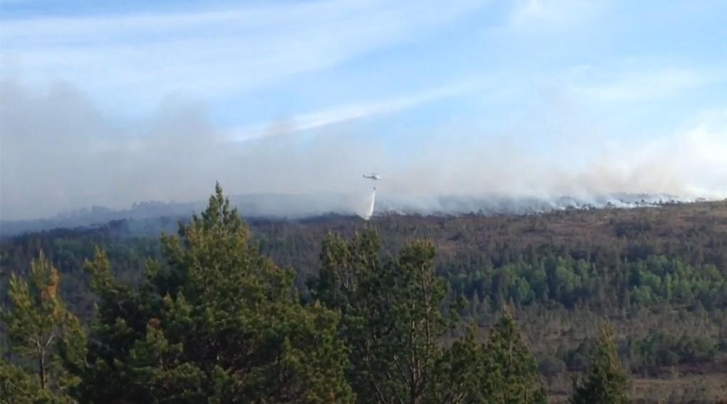 SLUKKER FRA LUFTEN: Et helikopter er i full gang med å slukke brannen.