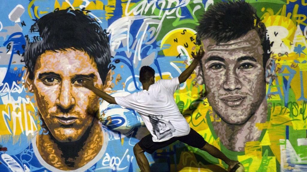 SUPERSTJERNER: En ung brasilianer spiller fotball foran et veggmaleri av Argentinas Lionel Messi og Brasils Neymar i favelaen Tavares Bastos i Rio de Janeiro. Vi tror superstjernene møtes i finalen 13. juli.