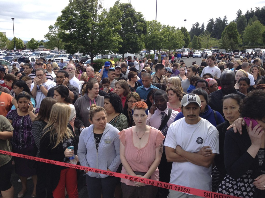 VENTER: Foreldre venter bak politisperringer på å bli gjenforent med sine barn etter skoleskytingen på Reynolds High School tirsdag.