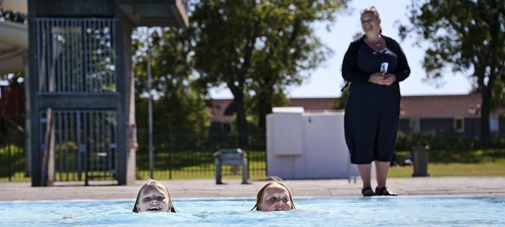 KAN SVØMME: Natalie Sannes Norheim (12) og Pernille Narten (13) lærte å svømme på barneskolen. De er glade for at det nå blir gitt gratis svømmeopplæring for tenåringer. På bassengkanten ser vi leder av kulturutvalget i kommunen, Camilla Eidsvold