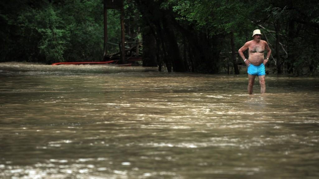 ALBENA: En turist går langs en oversvømt vei i turistområdet Albena ved Svartehavet lørdag. 1200 turister ble evakuert fra hoteller i Albena lørdag.