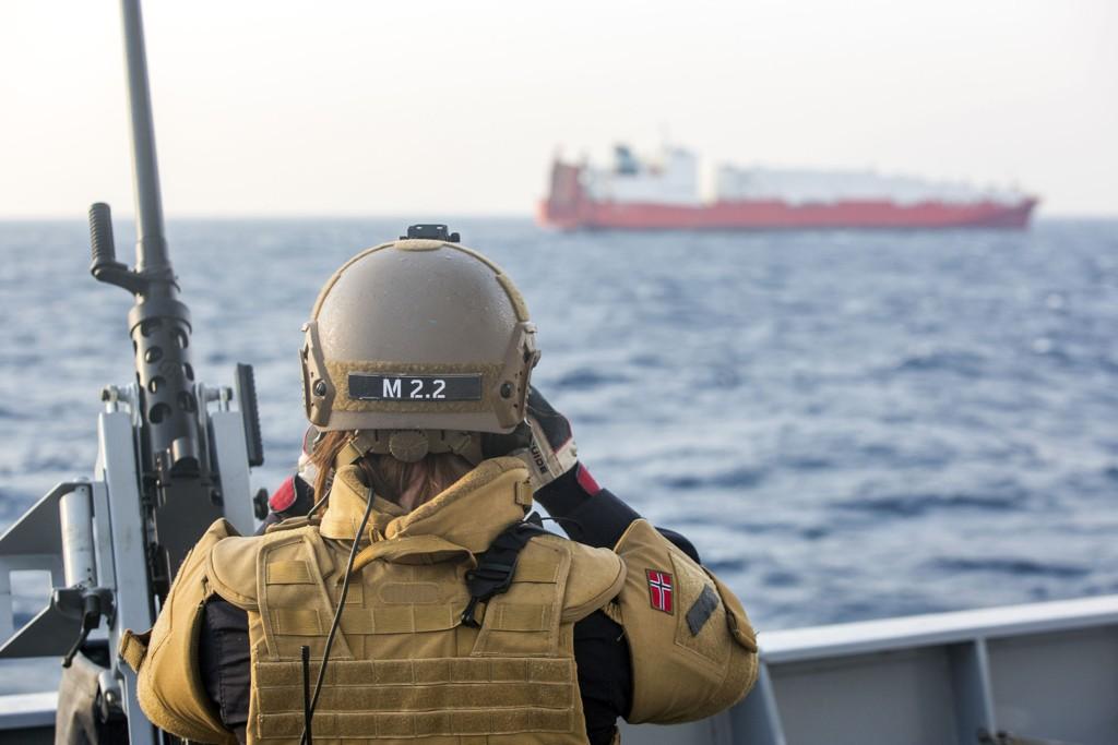 En norsk soldat på KNM «Helge Ingstad» holder utkikk med det norske lasteskipet «Taiko» som har vært med på og frakte vekk 1.300 tonn kjemiske våpen fra Syria.