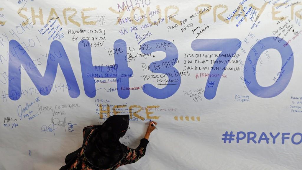 En kvinne skriver en bønn for passasjerene på det savnede Malaysia Airlines-flyet, flight MH370.