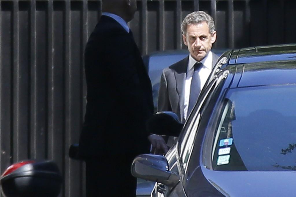 Ekspresident Nicolas Sarkozy (t.h.) forlater boligen sin i Paris onsdag. Han ble samme dag siktet for korrupsjon.