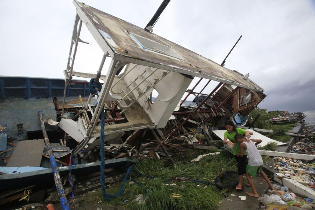 Innbyggere ved en båt som ble kastet på land av den sterke vinden onsdag.