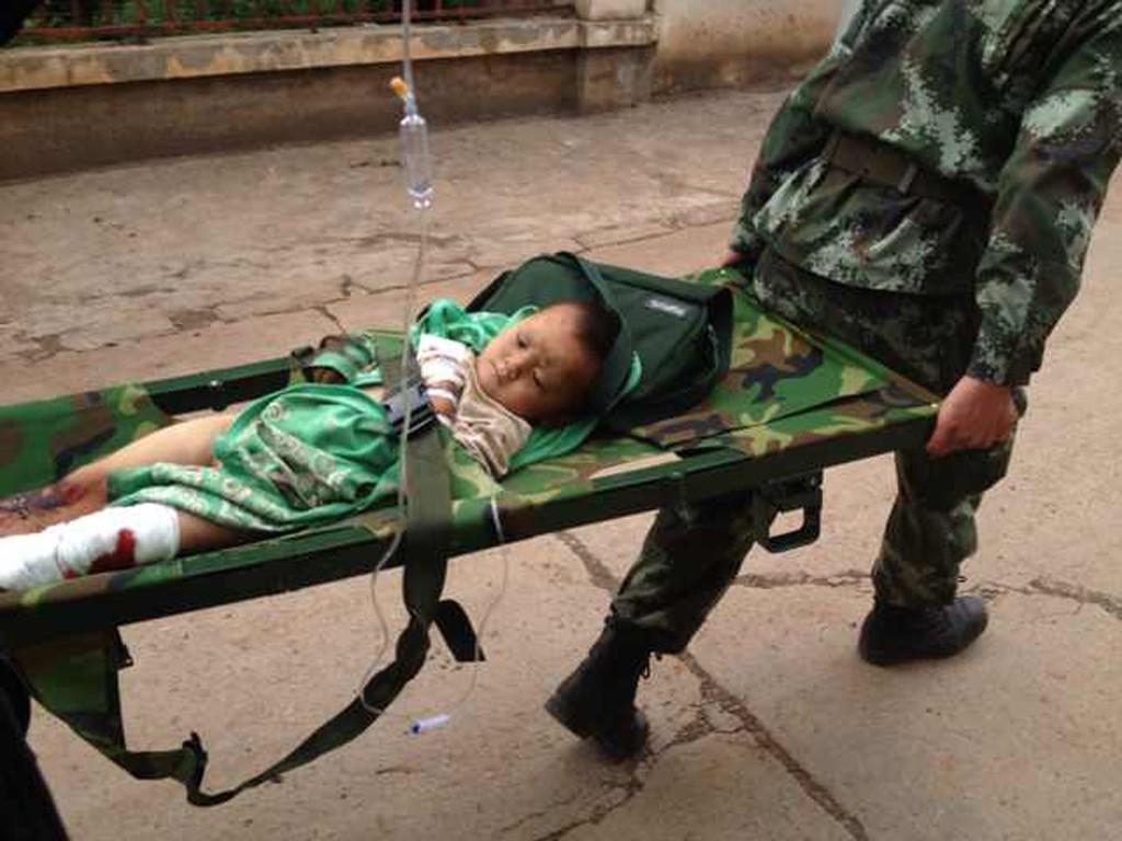 SKADD: Hjelpearbeidere bærer vekk en skadd unge etter jordskjelvet i Kina søndag.