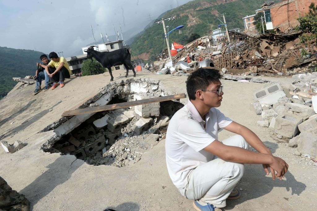 Jordskjelvsofre tar en hvilepause midt i ruinene.