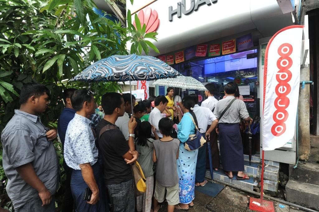 Folk står i kø for å kjøpe abonnement av Ooredoo, selskapet Telenor er deleier av i Myanmar.