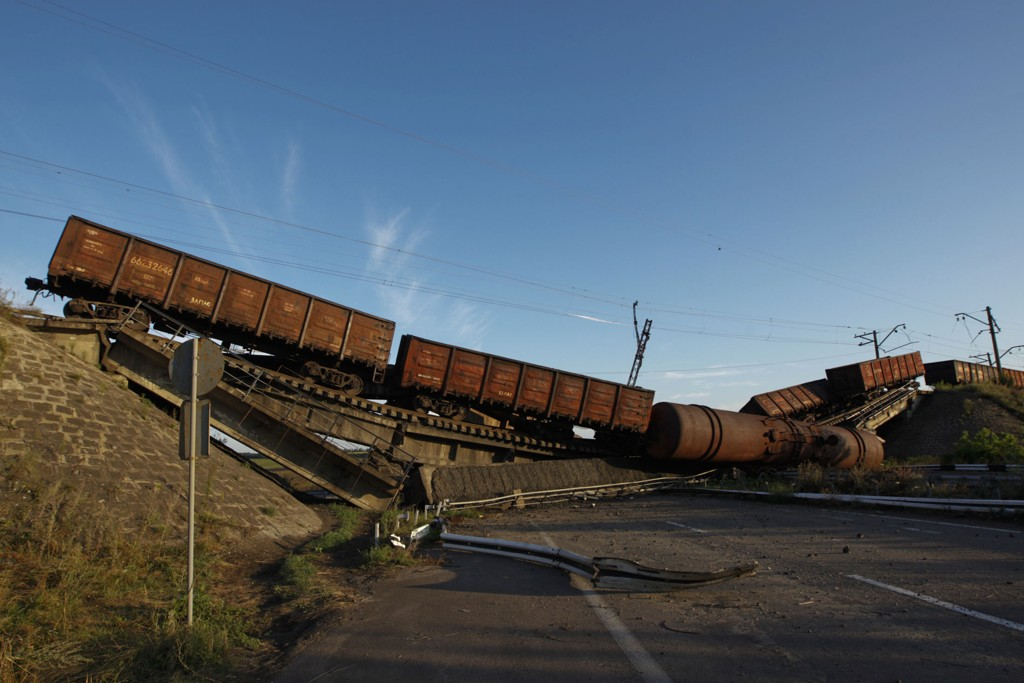 ØDELAGT: En togvogn på en ødelagt jernbanebru like ved en av hovedveiene utenfor Donetsk øst i Ukraina. Jernbanebrua ble ødelagt i kamper mellom regjeringsstyrker og prorussiske opprørere. Foto: NTB scanpix