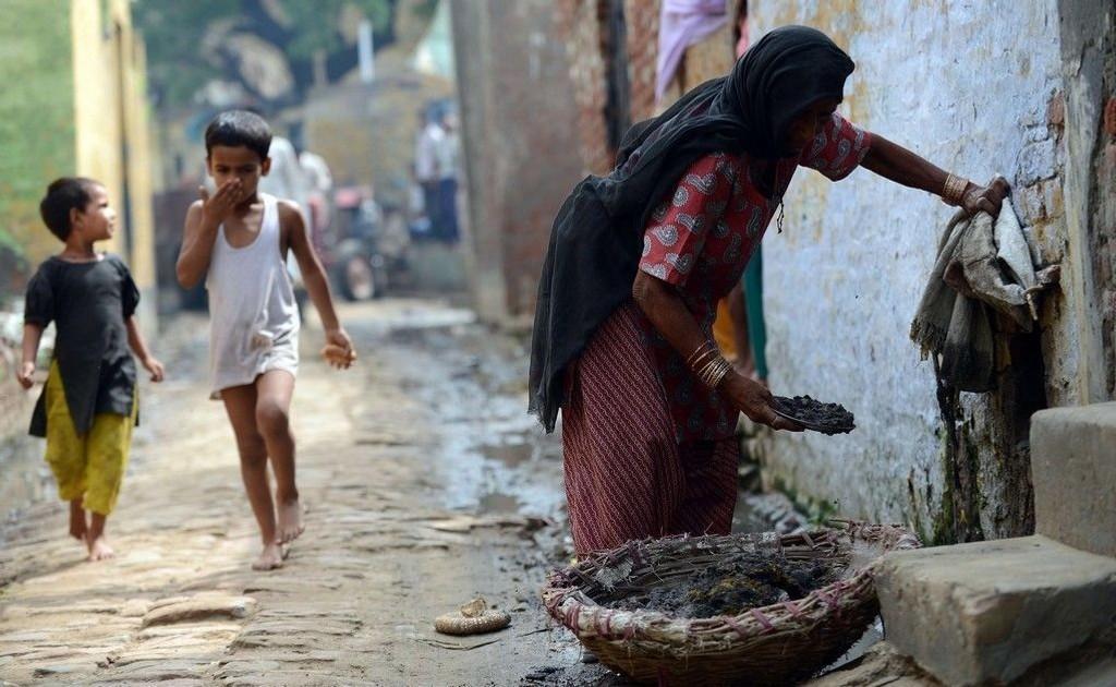 En 60 år gammel kvinne fjerner avføring for anre mennesker i landsbyen Nekpur øst for New Delhi. Bildet er tatt i august 2012.
