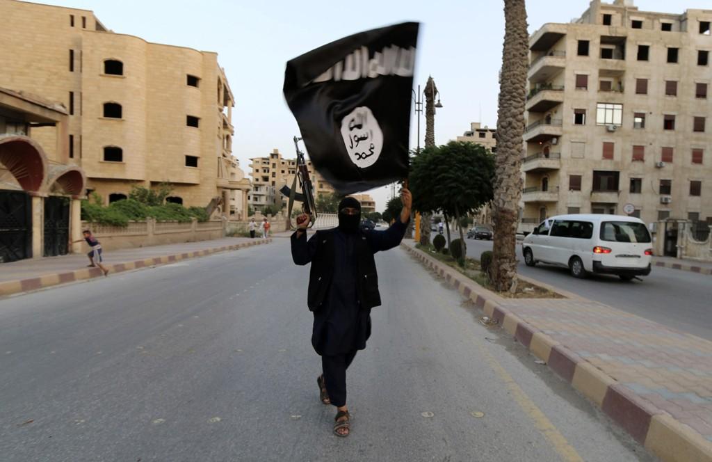 IS: Et medlem av terrorgruppen IS vifter med flagget i Ragga i juni.