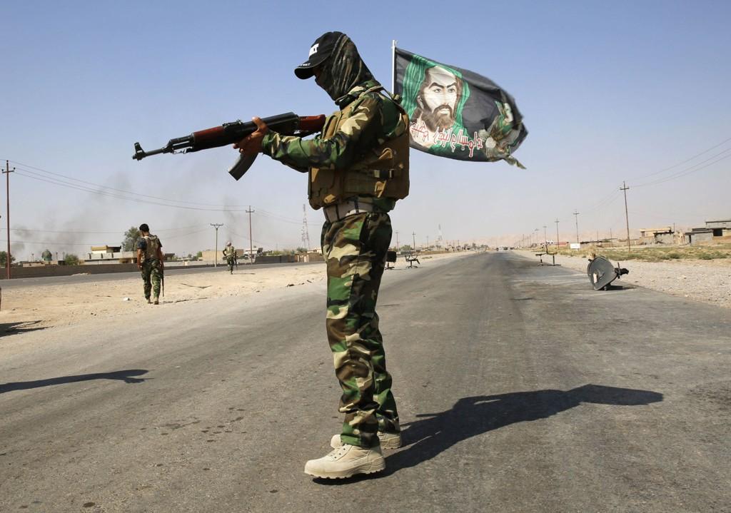 En soldat fra den sjiamuslimske Badr-brigaden er klar til kamp mot den sunniekstreme gruppa Den islamske staten (IS). Her holder soldaten vakt ved en kontrollpost utenfor byen Amerli, som nylig ble gjenerobret fra IS.