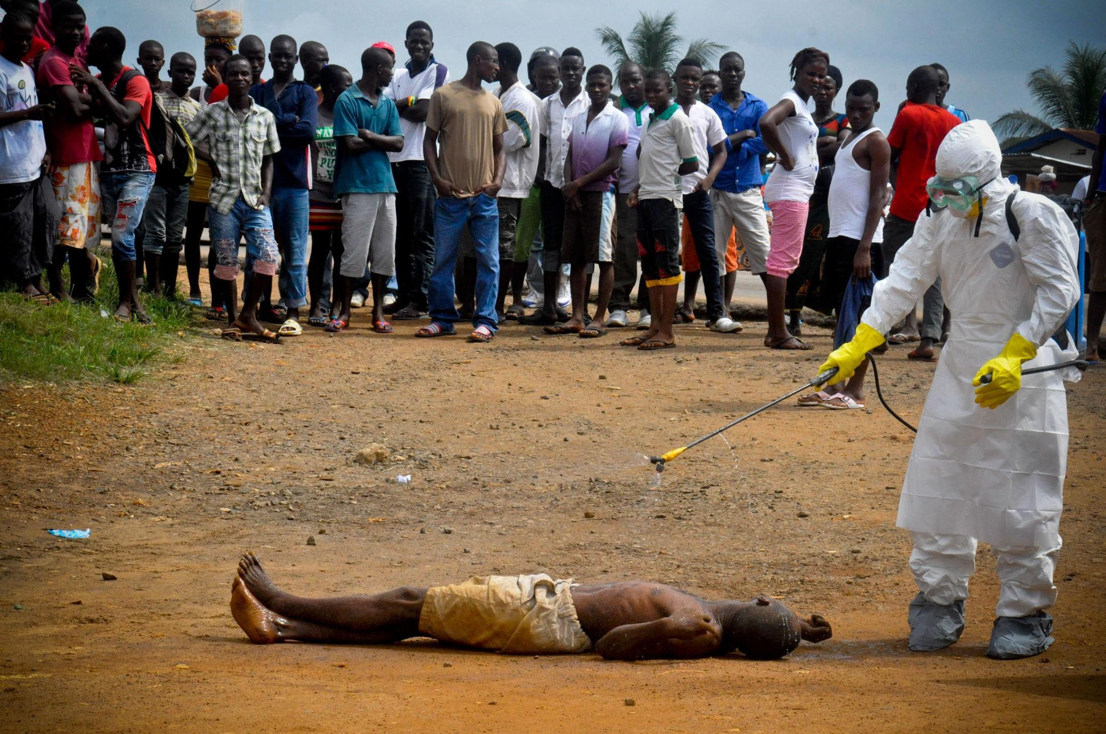 FALLER DØENDE OM PÅ VEIEN: En helsearbeider i verneutstyr sprayer desinfiserende middel over en mann de frykter dør av ebolaviruset. Bildet er tatt 4. september 2014. Verdens helseorganisajon har nå erkært ebolautbruddet som ute av kontroll, og er ute av stand til å behandle alle som blir syke.