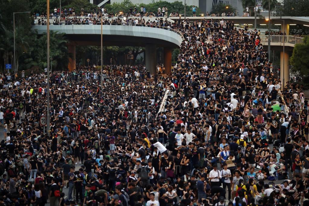 Demonstranter blokkerer hovedveien inn til finansdistriktet i Hongkong nær regjeringens hovedkvarter mandag.