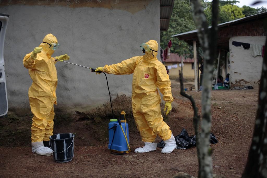 DØDELIGSTE I HISTORIEN: Over 3000 mennesker har dødd av ebola siden det brøt ut tidligere i år. Her desinfiserer to hjelpearbeidere hverandre i landsbyen Freeman Reserve i Liberia.