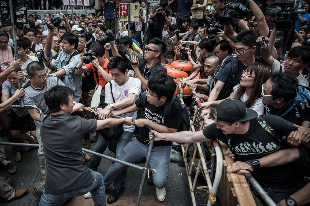 Dempkratiforkjempere forsøker å beskytte en barikade fra andre protestanter i Mongkok området i of Hongkong.