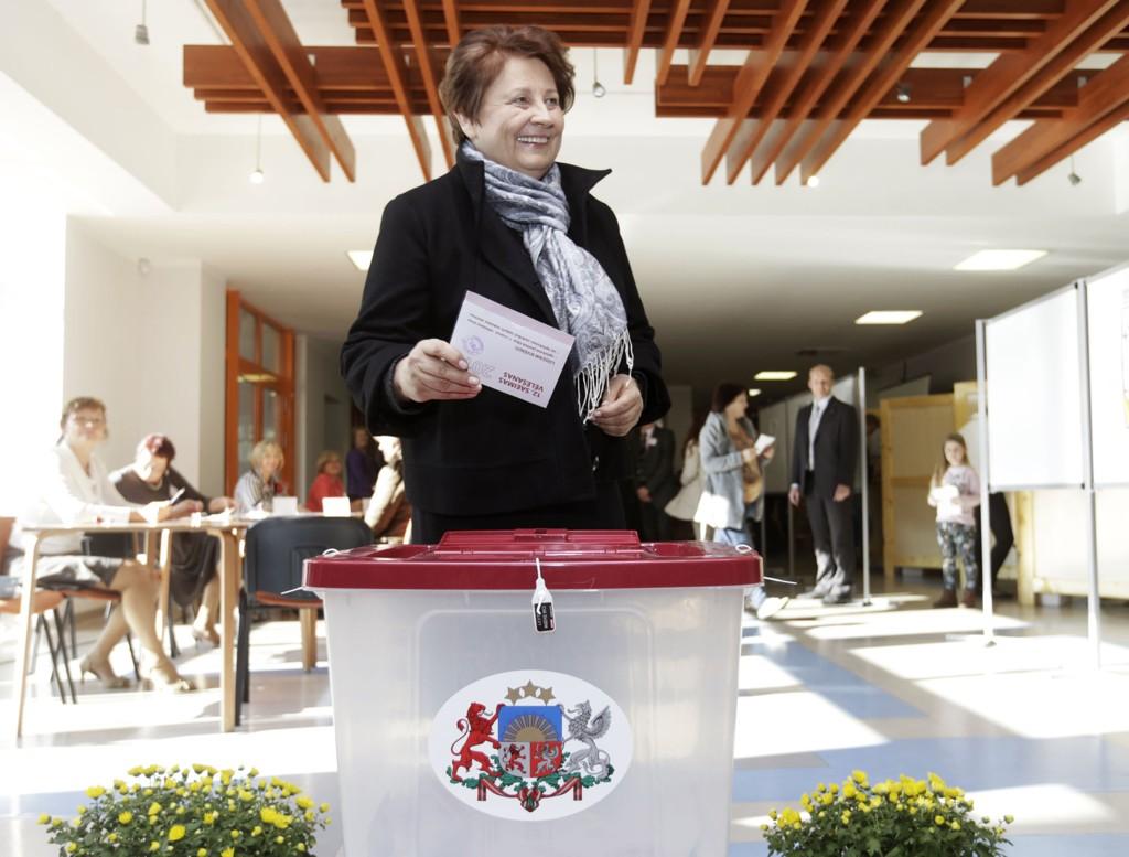 Latvias statsminister Laimdota Straujuma legger en stemmeseddel i valgurnen i Jaunmarupe under nasjonalvalget i Latvia lørdag.