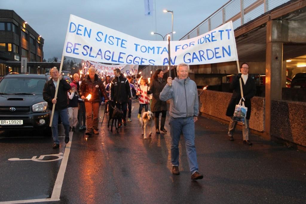 DEMO: Idrettslederen Terje Sand gikk i spiss for fakkeltoget. Første fane bæres av politikerne Arild Gjervan (H) og Terje Bjøro (V).