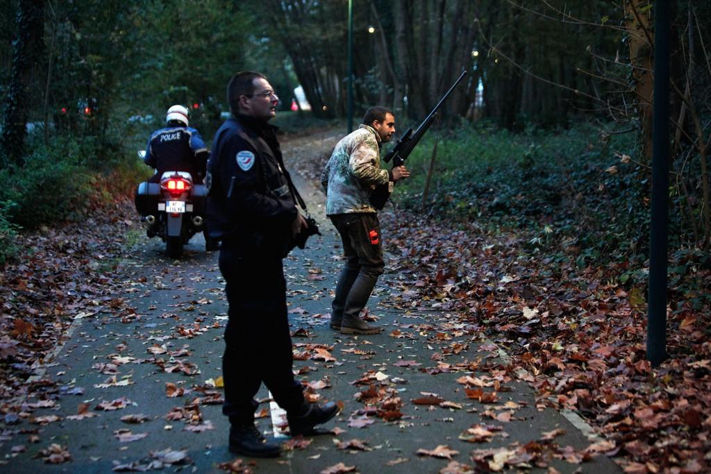 PÅ JAKT: Medlemmer av politiets dyrepatrulje går gjennom skogen ved Montevrain øst for Paris.