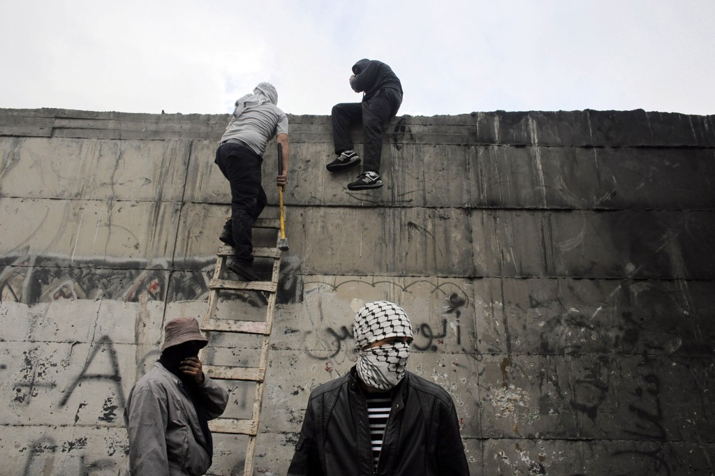 Palestinske demonstranter klatrer opp en stige foran den omstridte muren som deler Abu Dis fra Jerusalem på Vestbredden.