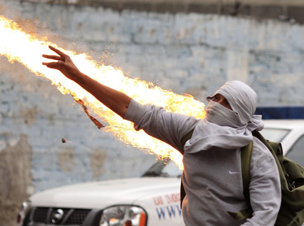 En maskert demonstrant kaster en bensinbombe mot opprørspolitiet i Mexico by. Demonstrasjonene har pågått siden 43 mannlige studenter ble bortført – angivelig av korrupt politi som ga dem til bandemedlemmer