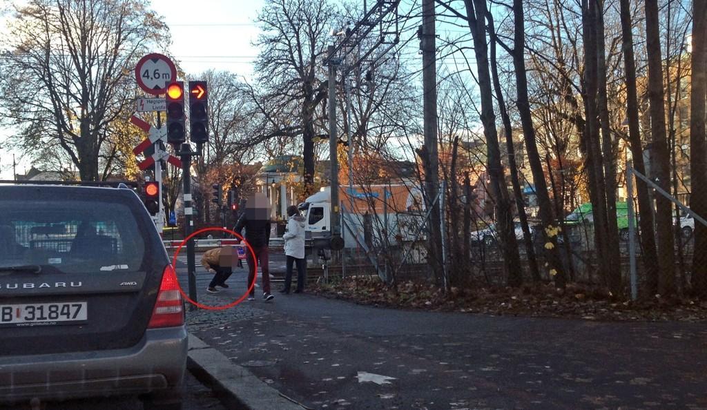 BOMMENE NEDE: Her krysser to personer planovergangen rett før toget kom kjørende fra stasjonen.