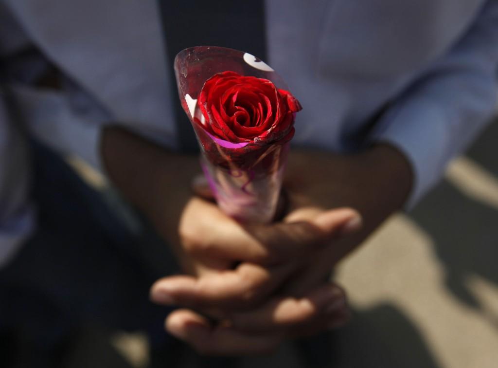 En pakistansk student i Karachi i Peshawar holder en rose og ber for ofrene etter terrorangrepet tirsdag.