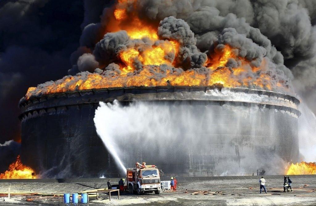I Es Sider har minst 800.000 fat olje gått opp i flammer de siste dagene, etter at en lagertank ble truffet i et rakettangrep opplyser Libyas nasjonale oljeselskap. Brannmenn i arbeid med å forsøker å slukke brannen mandag 29 desember.