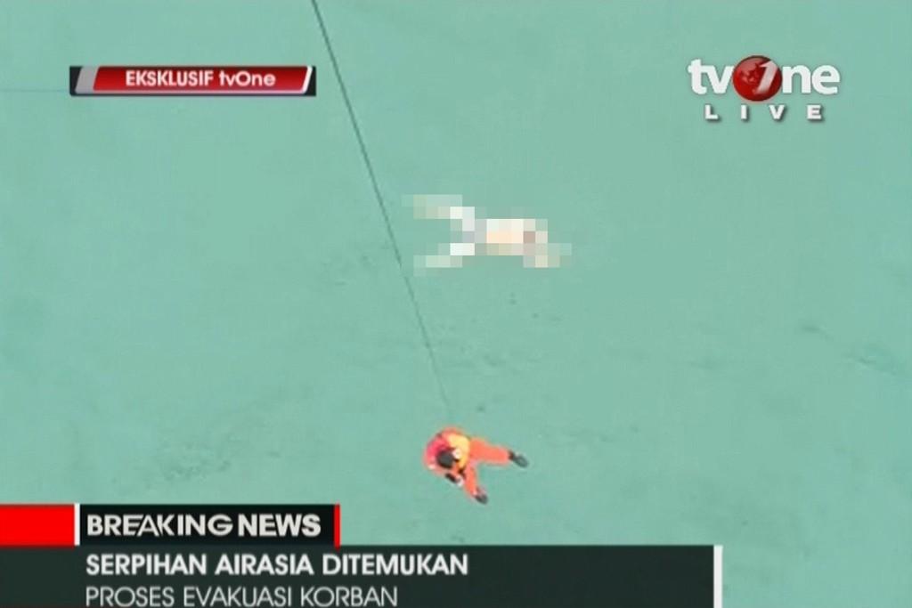 TV-bilder viser redningsmannskap i ferd med å hente opp døde fra havet.