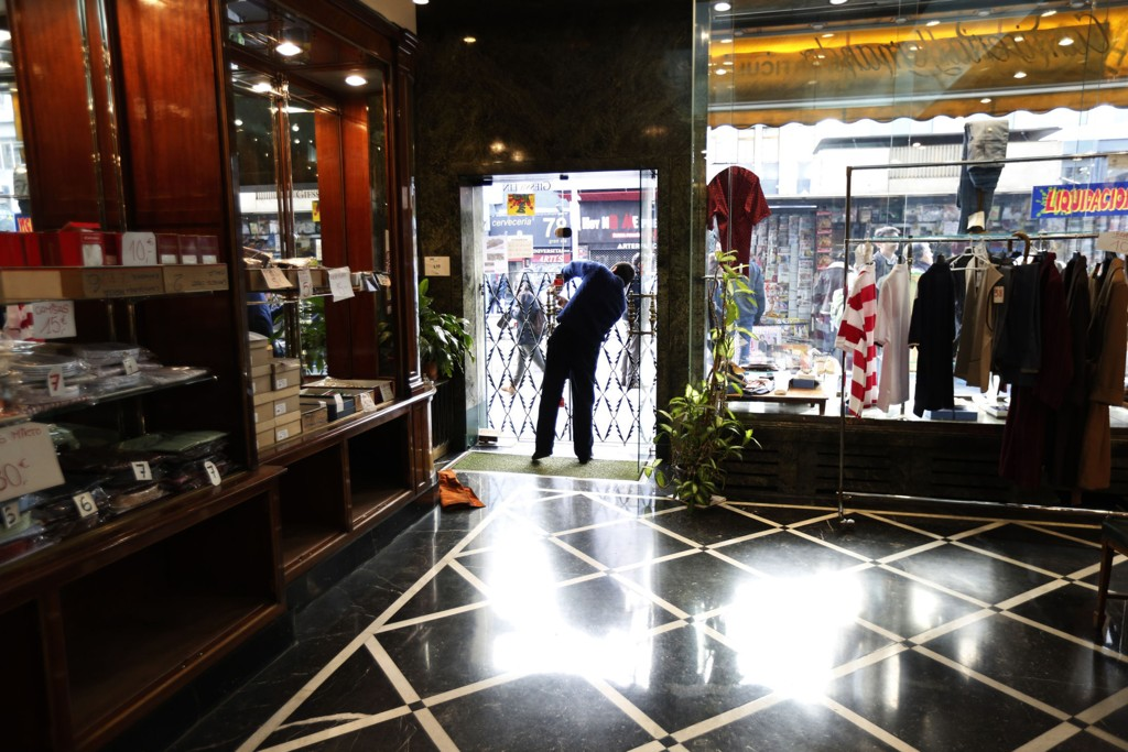 Etterspørselen i eurolandene er så lav at prisene står i fare for å synke. Her stenger en ansatt en skjortebutikk i sentrum av Madrid, som i 57 år er blitt drevet av familien Angel Garcia. Mange selvstendig-drevne butikker kan bli tvunget til å stenge i Spania som følge av at 30 år gamle leieavtaler utløper.